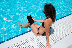 Female in black swimwear holding touch pad with blank copy space screen for your advertising content while relaxing outside Stock Images