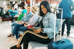 Female black tourist with suitcase in airport. Female black tourist with suitcase waiting for departure in airport. Passengers with baggage looking forward to stock image