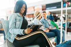 Female black tourist with suitcase in airport. Female black tourist with suitcase waiting for departure in airport. Passengers with baggage looking forward to royalty free stock photos