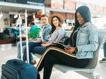 Female black tourist with suitcase in airport. Female black tourist with suitcase waiting for departure in airport. Passengers with baggage looking forward to royalty free stock images