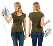 Female with blank green shirt holding an iron. Photo of a teenage female with long blond hair posing with a blank green shirt and holding an iron.  Front and Royalty Free Stock Photos