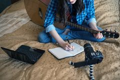 Female blogger closeup on the bed with a guitar, composes music and writes vlog on DSLR camera and laptop. Female blogger closeup on the bed with a guitar Stock Photo