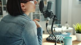 Female blogger recording audio in sound studio talking in microphone. With serious face sitting at desk alone. Blogging, business and modern devices concept stock video