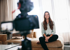 Female blogger recording video content for her blog. Young woman recording video on camera mounted on a tripod for her vlog. Pretty woman smiling at the camera Royalty Free Stock Images
