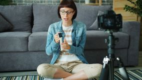 Female blogger recording video about digital watch using camera in apartment. Female blogger young lady is recording video about digital watch using camera in stock footage