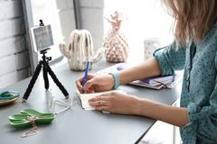 Female blogger recording video. At table royalty free stock photo
