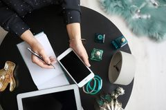 Female blogger with smartphone and notebook. At table, closeup Stock Image
