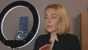 Female blogger takes the stream with your smartphone and the led rings light