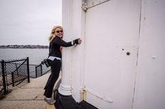 Female blond woman hugs the Portland Breakwater Lighthouse, aka Bug Lighthouse. Female blond woman hugs the Portland Breakwater Lighthouse, also known as the Bug stock image