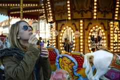Soap Bubbles. A female blonde model blowing soap bubbles at a merry-go-round Royalty Free Stock Image