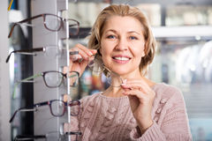 Female blonde selects spectacles at the display. Mature positive female blonde selects spectacles at the display Stock Photos