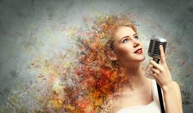 Female blonde singer. Image of female blondу singer holding microphone against color background Royalty Free Stock Photos