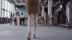 Female blonde team leader walking through office and controls work of employee. Female looks the fabric examples slow mo stock footage