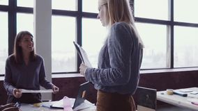 Female blonde team leader walking through office and controls work of employee. Female looks the fabric examples stock footage