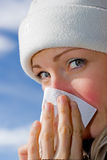 Female blowing nose. Female blowig her nose (blue sky background Royalty Free Stock Photo