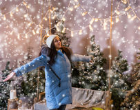 Female in blue down jacket rejoicing because of snowing standing. Near a swing with a blanket under the flashlights in a snow-covered park with spruce trees Stock Photos
