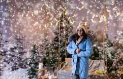 Female in blue down jacket standing near bench or a swing with a. Blanket under the flashlights in a snow-covered park with spruce trees, wearing warm woolen Stock Photos