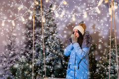 Female in blue down jacket warming hands in mittens under the fl Stock Photography