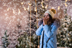 Female in blue down jacket warming hands under the flashlights i Stock Photo