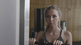 Woman Lifting Weight. Female body builder using a weights machine in the gym.Active woman workout triceps muscles pulling cable machine in fitnesss club in slow stock video