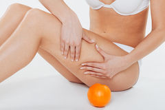 Female body with orange on a white background Stock Photography