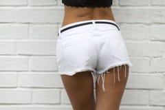 Female body part denim jeans shorts. Closeup Female body part white jeans shorts Stock Photography