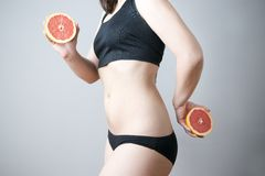 Female body with red grapefruit. On gray background. Weight loss, diet Stock Image