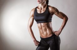 Female body. The body sports an attractive woman on gray background Royalty Free Stock Images
