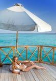 The female body sunbathes on a beach against the sea Stock Photos