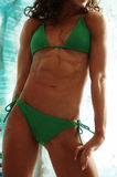 Female bodybuilder. Curvy female athlete in green bikini torso with nice defined abdomen muscles Royalty Free Stock Image
