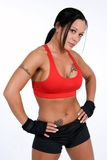 Female Bodybuilder. A female bodybuilder with tattoos poses in a red sports bra with hands wrapped stock photography