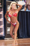 Female bodybuilder in abdominals and thighs pose and red bikini Stock Photos