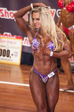 Female bodybuilder in abdominals and thighs pose on stage Stock Images