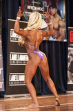 Female bodybuilder in back double biceps pose and pink bikini Royalty Free Stock Images