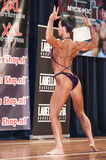 Female bodybuilder in back double biceps pose and purple bikini Royalty Free Stock Photography