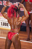 Female bodybuilder in back double biceps pose and red bikini Royalty Free Stock Images
