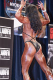 Female bodybuilder in back double biceps pose on stage Royalty Free Stock Photo