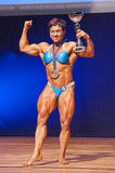 Female bodybuilder celebrates her championship victory on stage Royalty Free Stock Photo