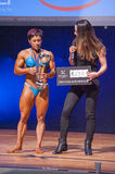 Female bodybuilder celebrates her championship victory on stage Stock Photography