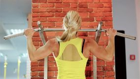 Female bodybuilder champion athlete gym, girl performs a pulling up exercise, healthy strong body beautiful young woman stock footage