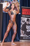 Female bodybuilder in double biceps pose and black bikini Stock Images