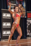 Female bodybuilder in double biceps pose and red bikini Royalty Free Stock Photos