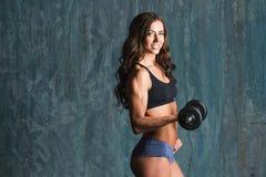 Female bodybuilder with dumbbells. stock photo