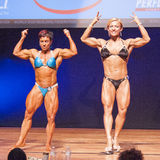 Female bodybuilder flexes her muscles presenting her physique in Royalty Free Stock Images