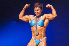 Female bodybuilder flexes her muscles presenting her physique in Royalty Free Stock Photo