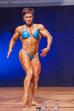 Female bodybuilder flexes her muscles presenting her physique in Royalty Free Stock Photos