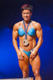 Female bodybuilder flexes her muscles presenting her physique in Stock Photography
