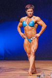 Female bodybuilder flexes her muscles presenting her physique in Stock Photo