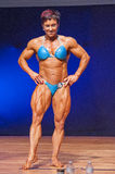 Female bodybuilder flexes her muscles presenting her physique Royalty Free Stock Photo