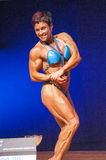 Female bodybuilder flexes her muscles presenting her physique Stock Image